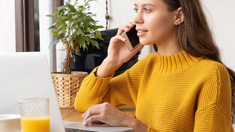 A girl in yellow dress is listening to the phone call while working on her laptop on the table.