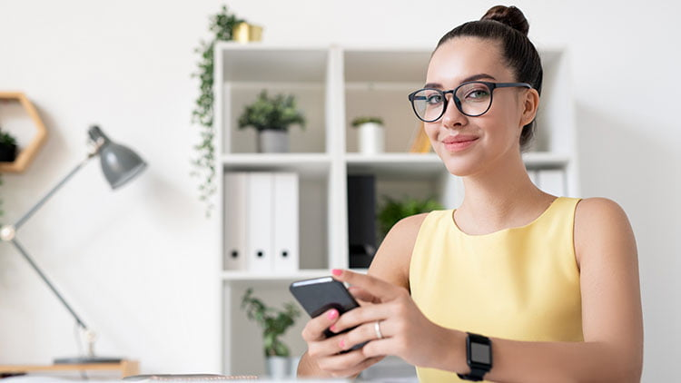 A marketing specialist girl is smiling having phone in her hand and sitting in her office..